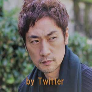 青のセーターに紺のマフラーをした松田賢二