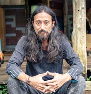 口髭と髪を伸ばし仙人の姿の松岡俊介
