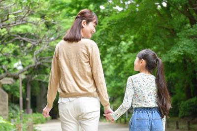 母親と子供が手をつなぎ散歩している